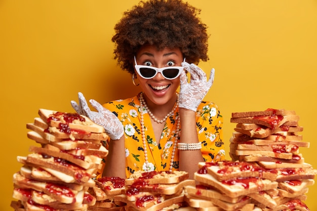 Attractive woman with afro hair surrounded by peanut butter jellly sandwiches