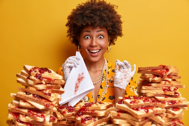 Привлекательная женщина с волосами афро в окружении бутербродов с арахисовым маслом