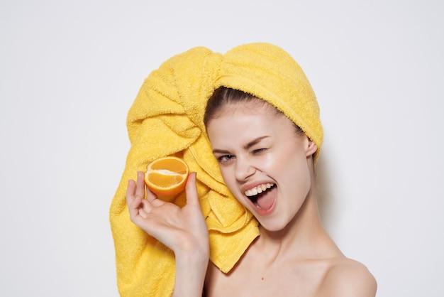 Привлекательная женщина с голыми плечами апельсины в руках чистая кожа. фото высокого качества