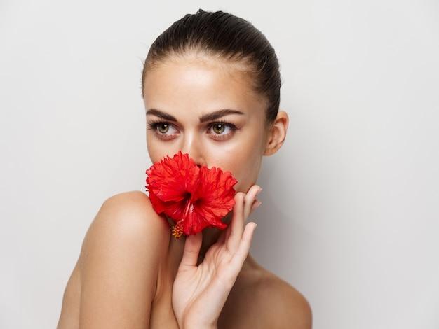 얼굴 근처 맨 손으로 어깨 붉은 꽃과 매력적인 여자