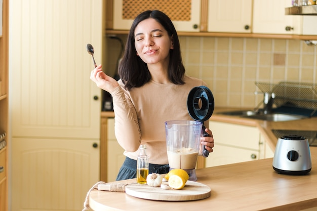 自然なベジタリアン料理自家製ひよこ豆のフムスレシピを準備するキッチンで美しい笑顔を持つ魅力的な女性