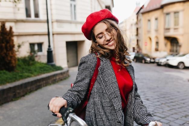 都市の背景に新しい灰色のツイードのコートでポーズをとって黒い爪を持つ魅力的な女性