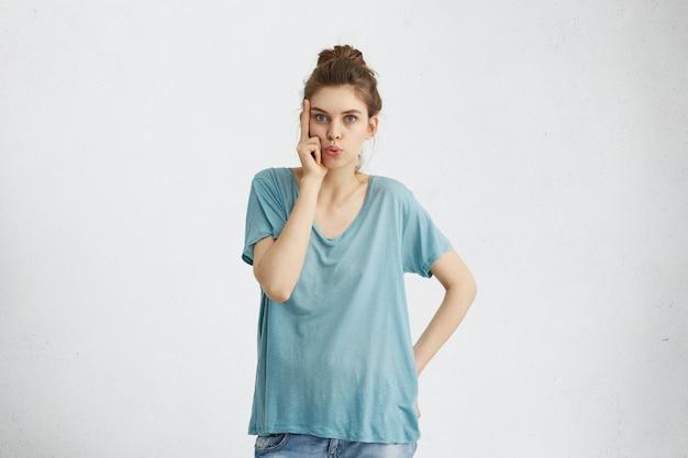 寺院に彼女の指を押しながら何かを滑走ルーズブルーのカジュアルなtシャツを着て青い暖かい目を持つ魅力的な女性。