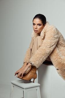 明るい化粧の魅力的な女性は、ファッショナブルなブーツのスツールに足を保持します