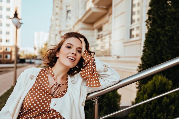 通りに立っている茶色の化粧の魅力的な女性。かわいい笑顔でデボネア短髪の女の子の屋外ショット。