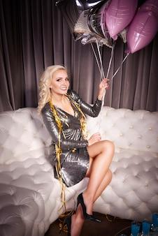 Donna attraente con un mazzo di palloncini seduta sul divano