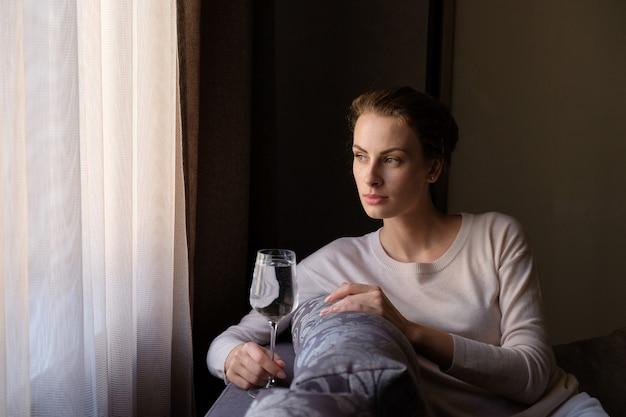 Привлекательная женщина с коктейлем в руке сидит дома на диване и смотрит в окно