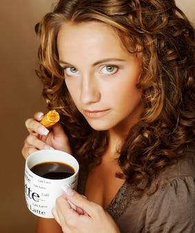 コーヒーとクッキーを持つ魅力的な女性