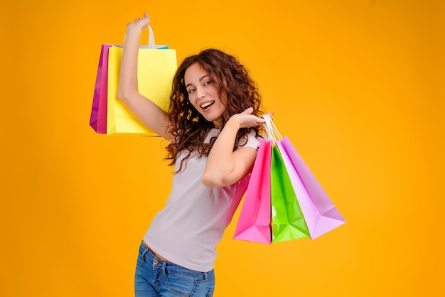 Attractive woman  with colorful shopping bags in her hands isolated over yellow background