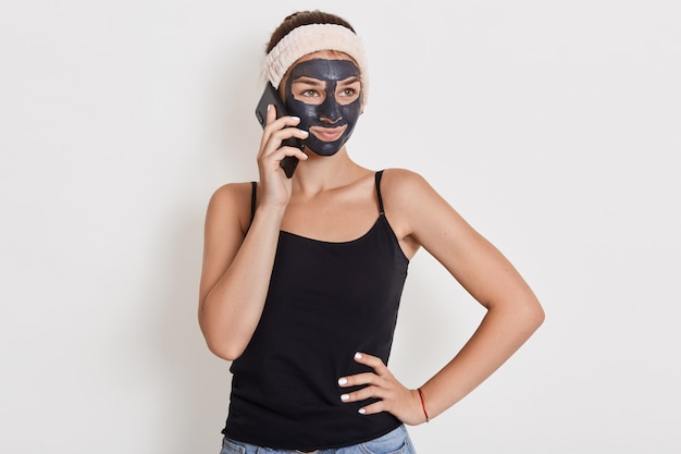 Attractive woman with cosmetic face clay mask talking via mobile phone while looking aside and keeping hand on hip, lady doing morning cosmetic procedures.