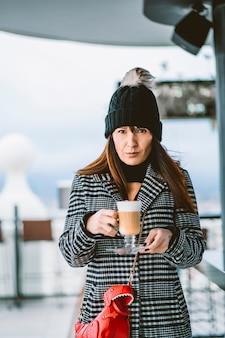 手でコーヒーカップを持つ魅力的な女性