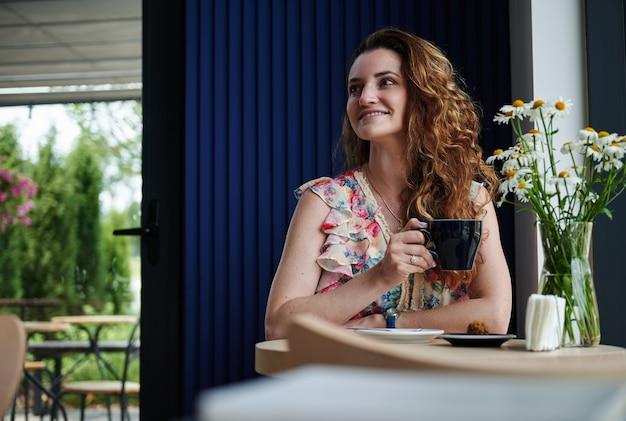 居心地の良い喫茶店のテーブルに座ってコーヒーを飲む巻き毛の魅力的な女性