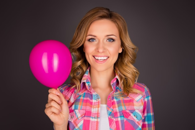 ピンクの風船でポーズをとる巻き毛の魅力的な女性