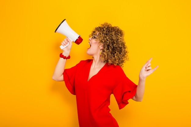 Attractive woman with curly hair with loudspeaker