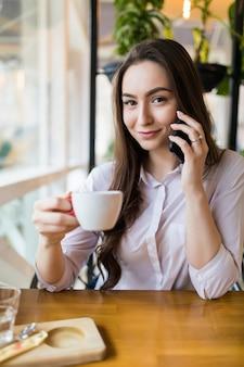 カフェで休んでいる間携帯電話で会話をしているかわいい笑顔の魅力的な女性
