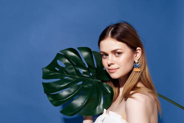 メガネのイヤリングファッション青い背景を持つ魅力的な女性