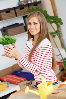Attractive woman with grass with plant pot