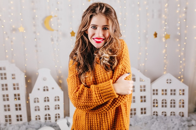 Attractive woman with gray eyes smiles amiably, hugging herself by shoulders. girl in knitted long sweater posing against wall of toy houses.