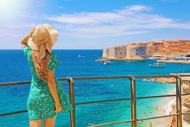 Привлекательная женщина в зеленом платье наслаждается видом на старый город дубровника, хорватия