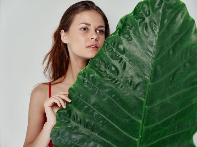 明るい背景のトリミングされたビューにヤシの木の緑の葉を持つ魅力的な女性