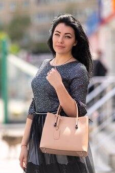 Привлекательная женщина с сумочкой позирует на открытом воздухе