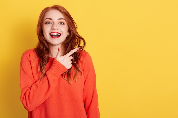 Attractive woman with happy expression pointing at copy space with index finger, dressed in casual orange sweater, models against yellow wall, ginger female with excited expression.
