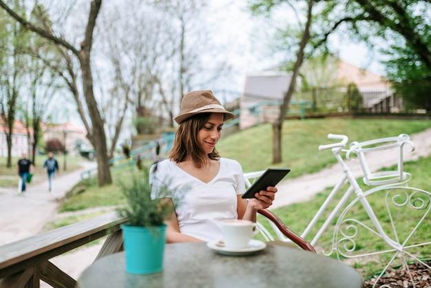 Attractive woman with hat sitting in outdoor cafe and using tablet.