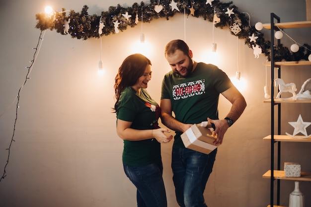 Una donna attraente con il suo ragazzo cauacsiano si fa regali e si sorprende prima di natale