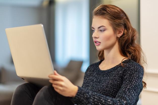 집에서 노트북으로 매력적인 여자입니다. 집에 앉아있는 동안 컴퓨터에서 작업하는 젊은 여자. 집에서 즐기는 시간.