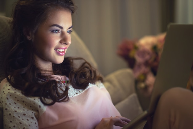 Attractive  woman with laptop at home. young woman working on computer while sitting on the  sofa at home. enjoying time at home. low key