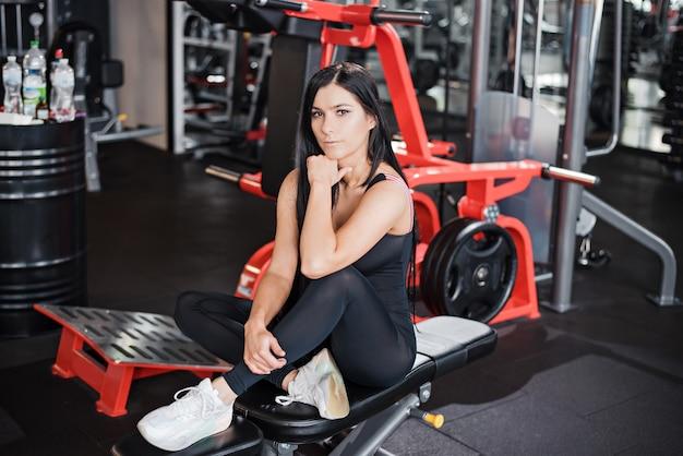긴 검은 머리를 가진 매력적인 여성이 체육관에서 운동한 후 벤치에서 휴식을 취합니다. 건강하고 활동적인 생활 방식의 개념입니다.