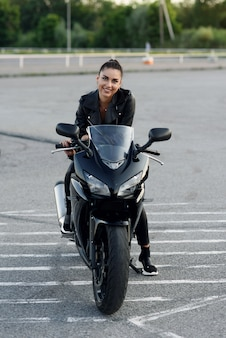 Attractive woman with long hair in black leather jacket and pants on outdoors parking with stylish sports motorcycle at sunset.