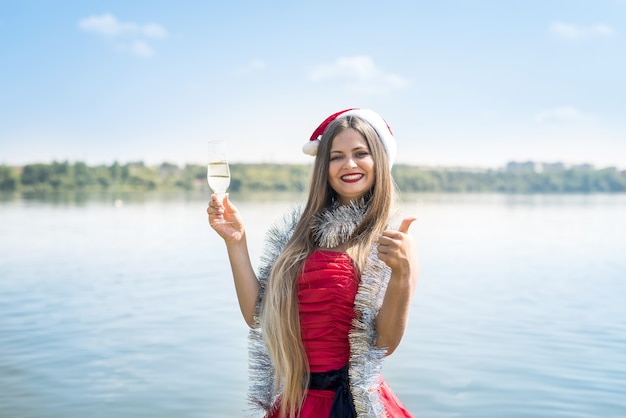 Attractive woman with long hair and champagne on beach