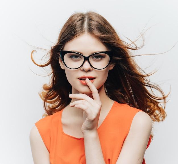 Привлекательная женщина с распущенными волосами, в очках и оранжевом сарафане