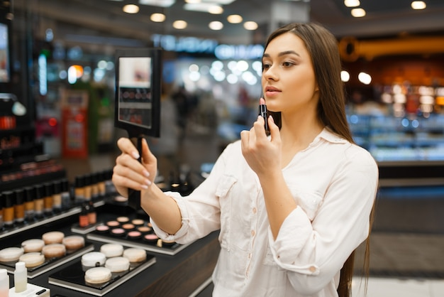 鏡を持つ魅力的な女性が化粧品店で口紅を塗る。高級美容室のショーケースのバイヤー、ファッション市場の女性客