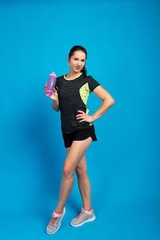 さわやかな水のボトルを保持している筋肉質の体を持つ魅力的な女性。健康の概念