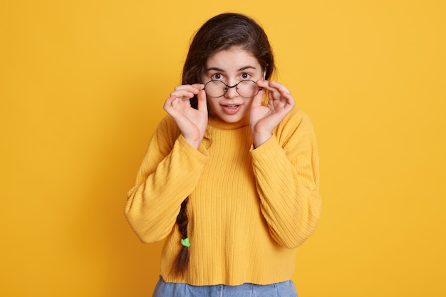 Attractive woman with new glasses keeping hands on her frame, posing isolated over yellow wall with astonished facial expression, wearing casual sweater.