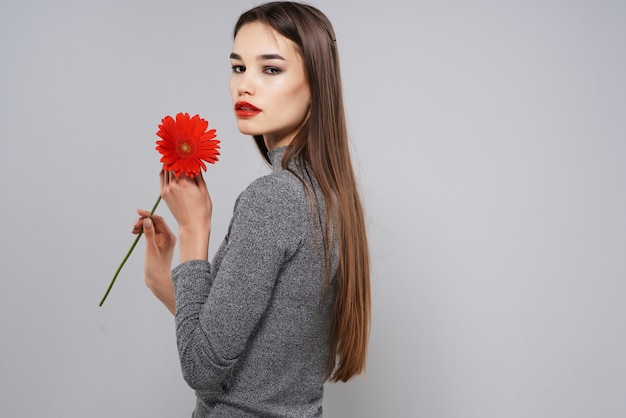 赤い花の魅力的なメイクの贅沢な魅力的な女性