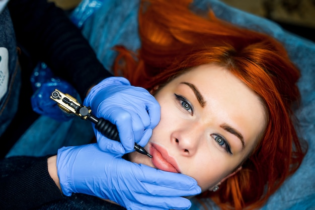 Attractive woman with red hair having permanent make-up on lips in beauty salon.