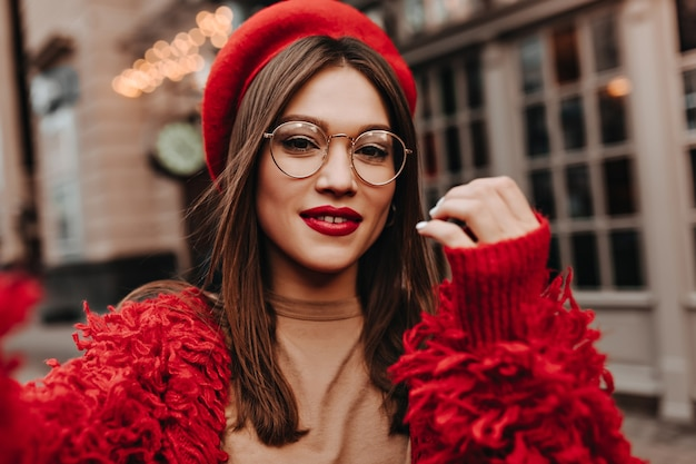 붉은 입술을 가진 매력적인 여자는 거리에 selfie를 만든다. 세련 된 모자, 빨간 재킷과 베이지 색 탑을 입은 안경에 갈색 머리의 총.