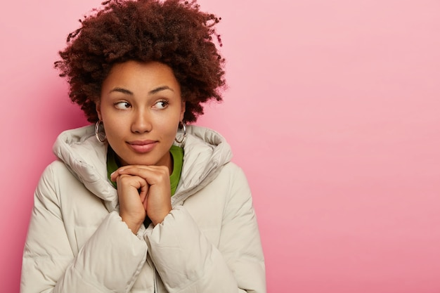 Attractive woman with serious look, dressed in outerwear, holds both hands together under chin, looks away, tries to warm, models over pink background, copy space