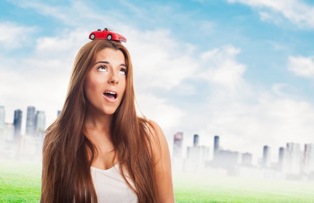 Attractive woman with a small red car on her head