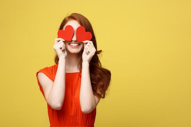 Привлекательная женщина с улыбкой с двумя маленькими красными сердцами в руках, закрывая глаза