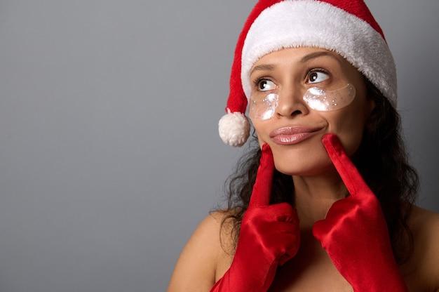 サンタクロースの帽子と赤いサテンの手袋を着用し、灰色の背景のコピースペースを見て、彼女の唇と笑顔に彼女の指を押して、滑らかな眼帯を持つ魅力的な女性。スパ、スキンケアのコンセプト