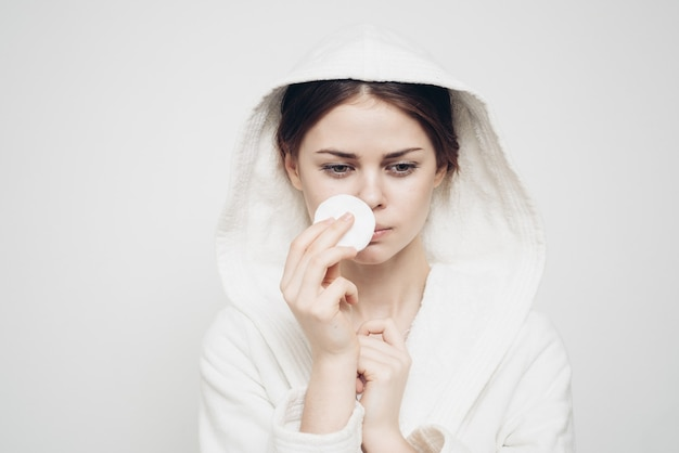 Attractive woman with sponge and in white dressing gown. high quality photo