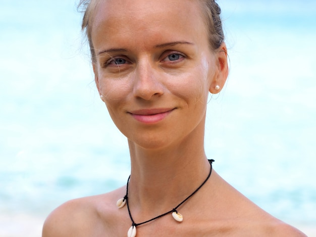 Attractive woman with sunscreen face cream on a tropical beach.