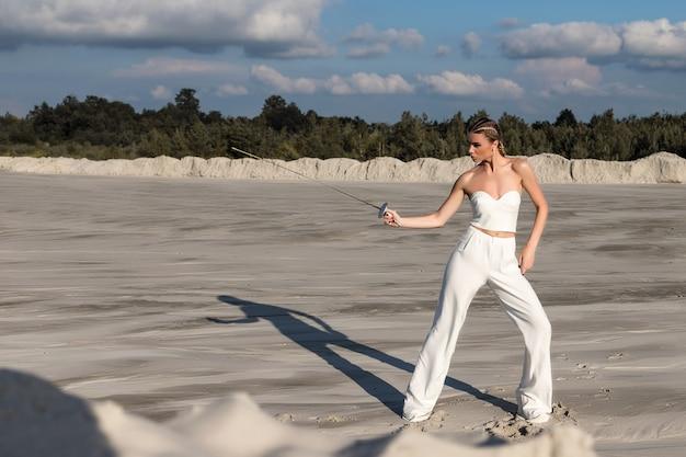 Привлекательная женщина с мечом в полностью белом наряде. модная съемка в пустыне