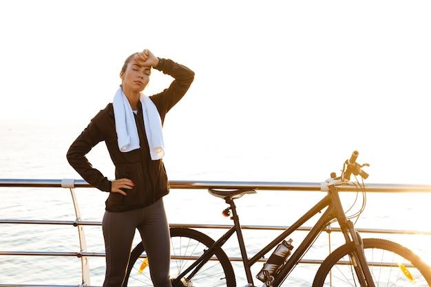 Привлекательная женщина с полотенцем на шее, стоя возле велосипеда на открытом воздухе, после тренировки на берегу океана