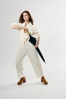 비 흰색 죄수 복 패션에서 손 보호에 우산을 가진 매력적인 여자.