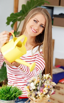 Attractive woman with watering can